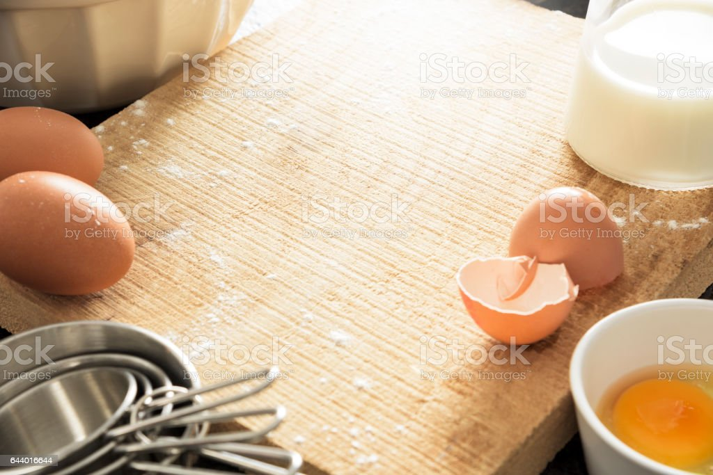 Wooden chopping board with copy space surrounded by baking ingredients stock photo