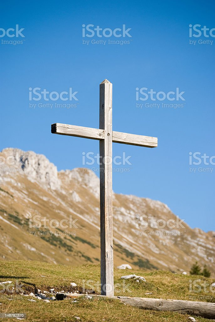 Wooden christian cross in mountains - vertical shot royalty-free stock photo