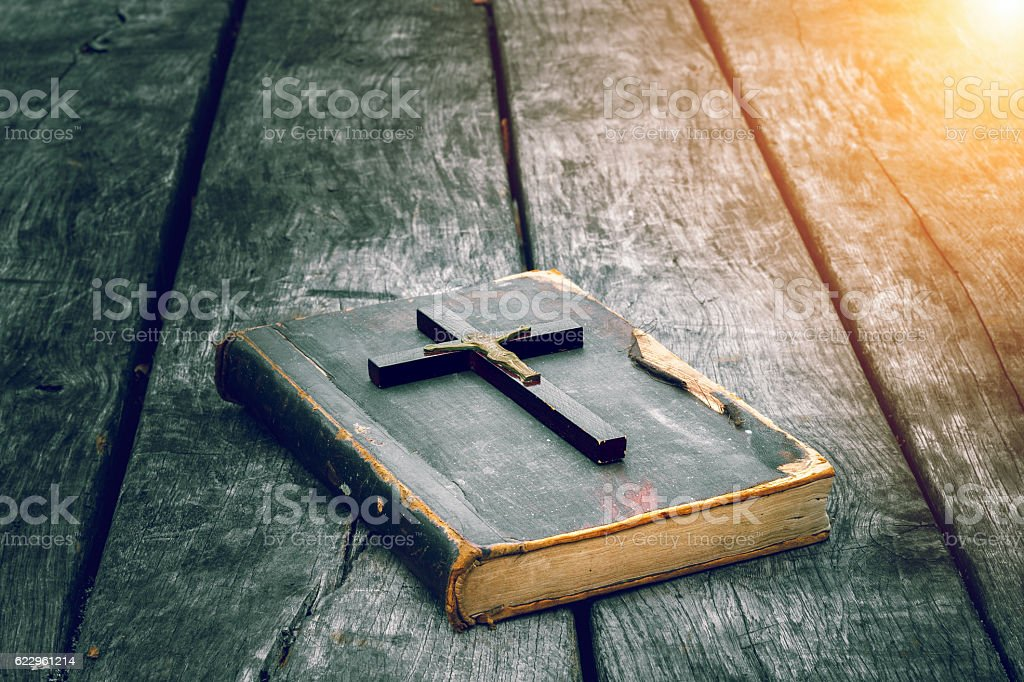 Wooden Christian cross on bible on the old table stock photo