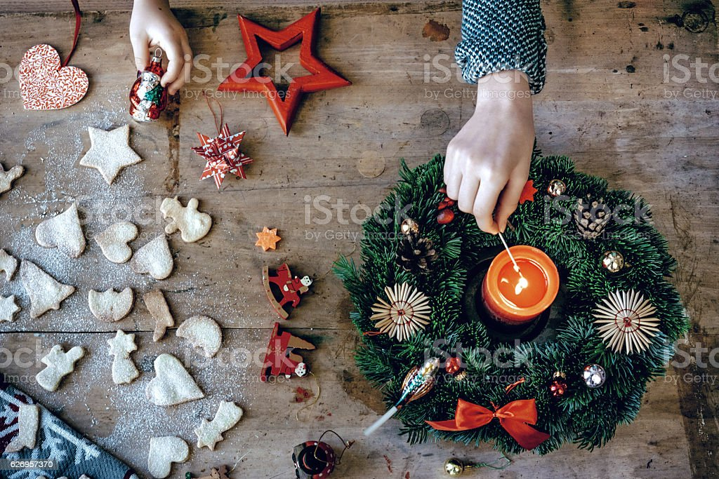 wooden christmas table with hand lighting Advent wreath stock photo