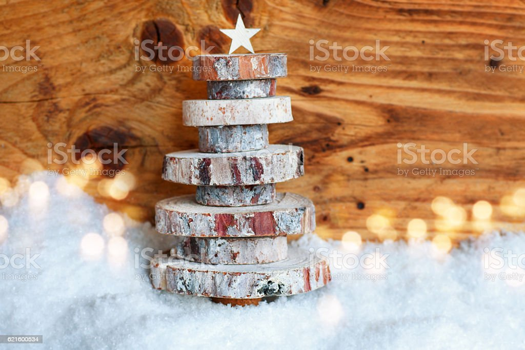 Wooden christmas tree in the snow stock photo