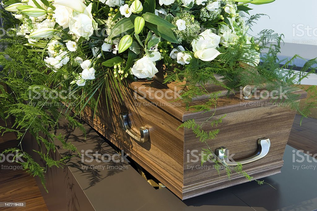 Wooden Coffin in a morgue with white flowers stock photo