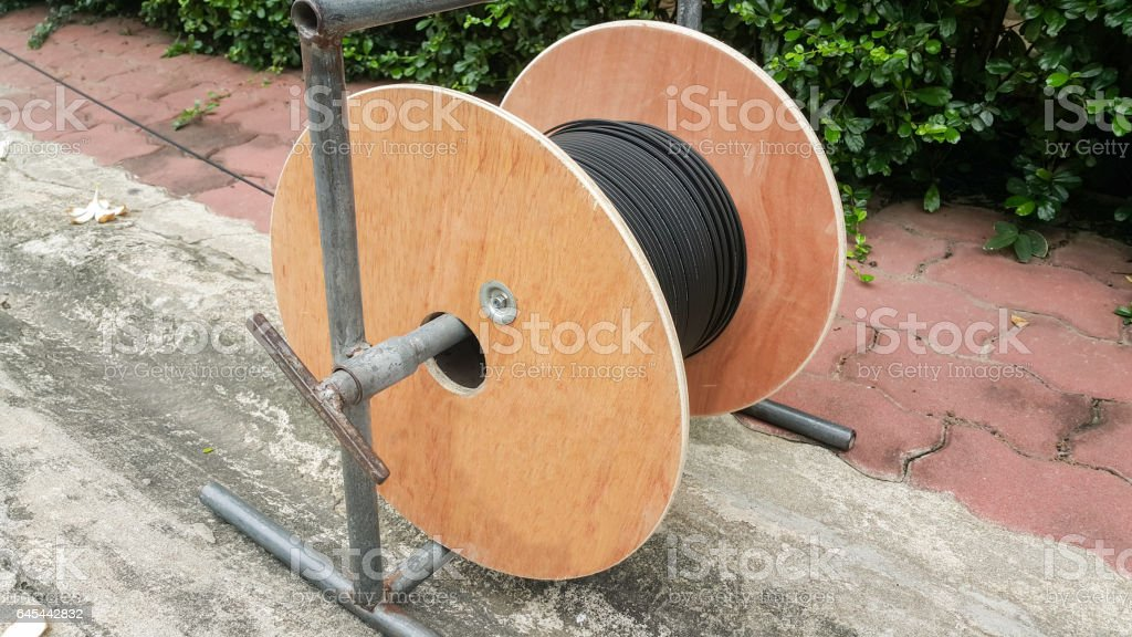 Wooden coil of electric and Fiber optic cable stock photo