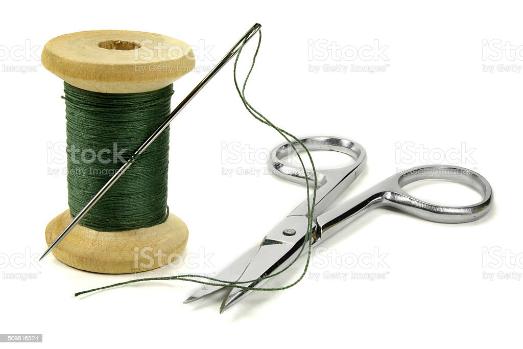Wooden coil with threads, needle and chromeplated scissors stock photo