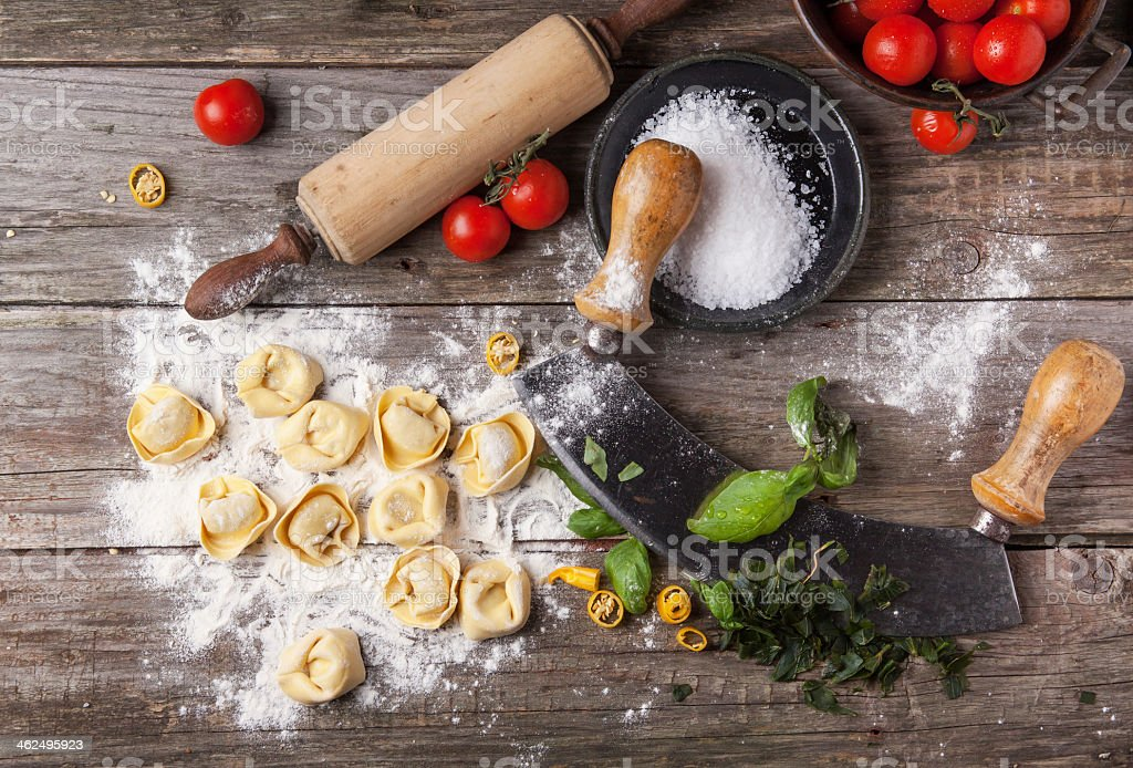 Wooden countertop with pasta ravioli flour and a rollin pin stock photo