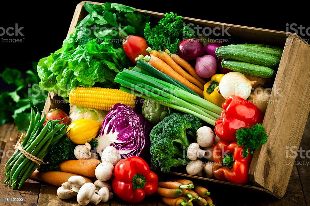 Wooden crate filled with fresh organic vegetables stock photo
