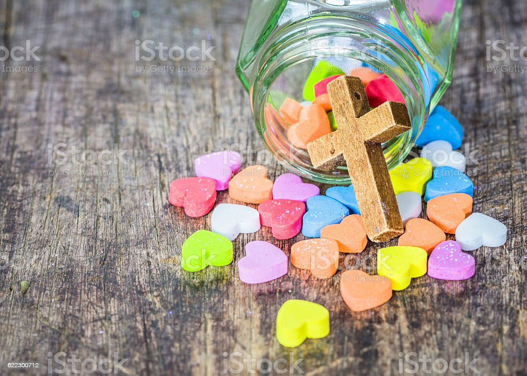 wooden cross and colorful hearts  in glass bottle stock photo