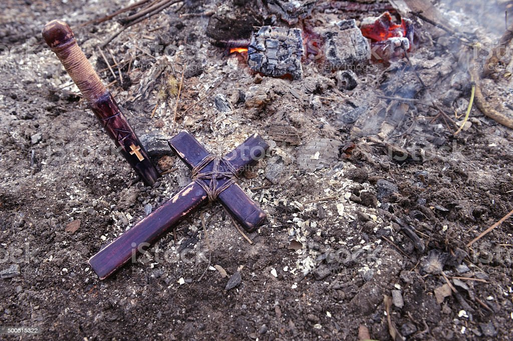 Wooden cross and stake on the ashes by fire stock photo