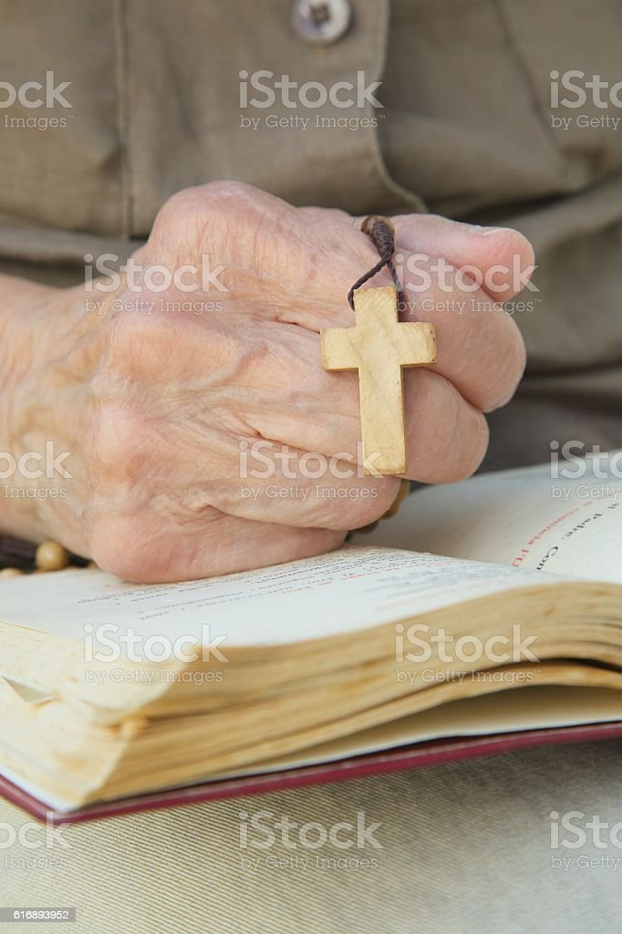 Wooden cross in the hand of senior woman stock photo