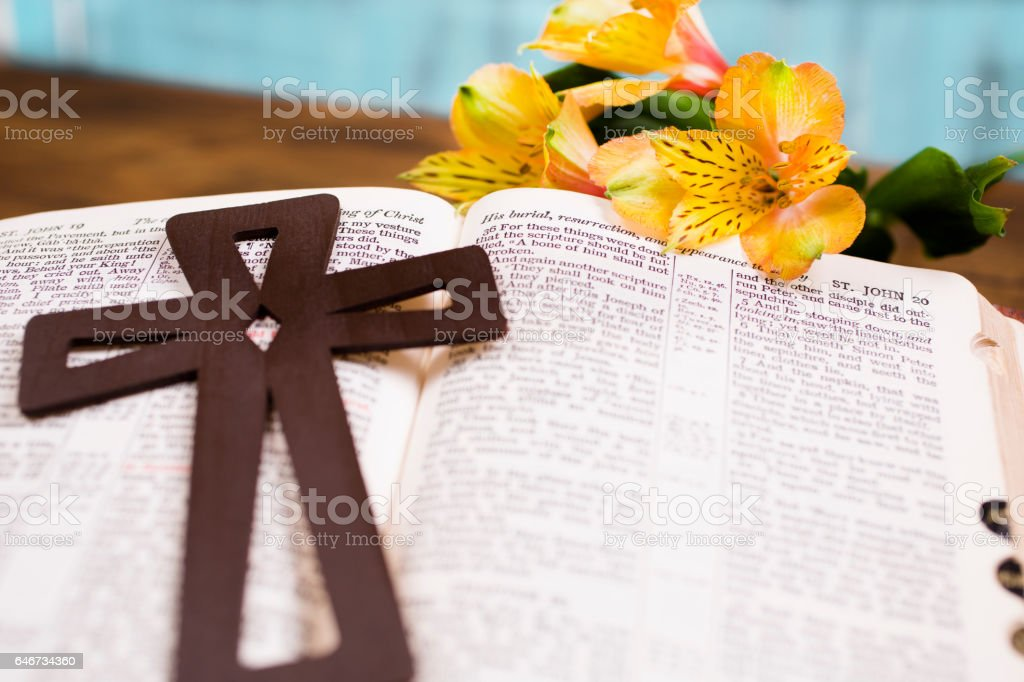 Wooden cross lies on open bible for Easter sunday. stock photo