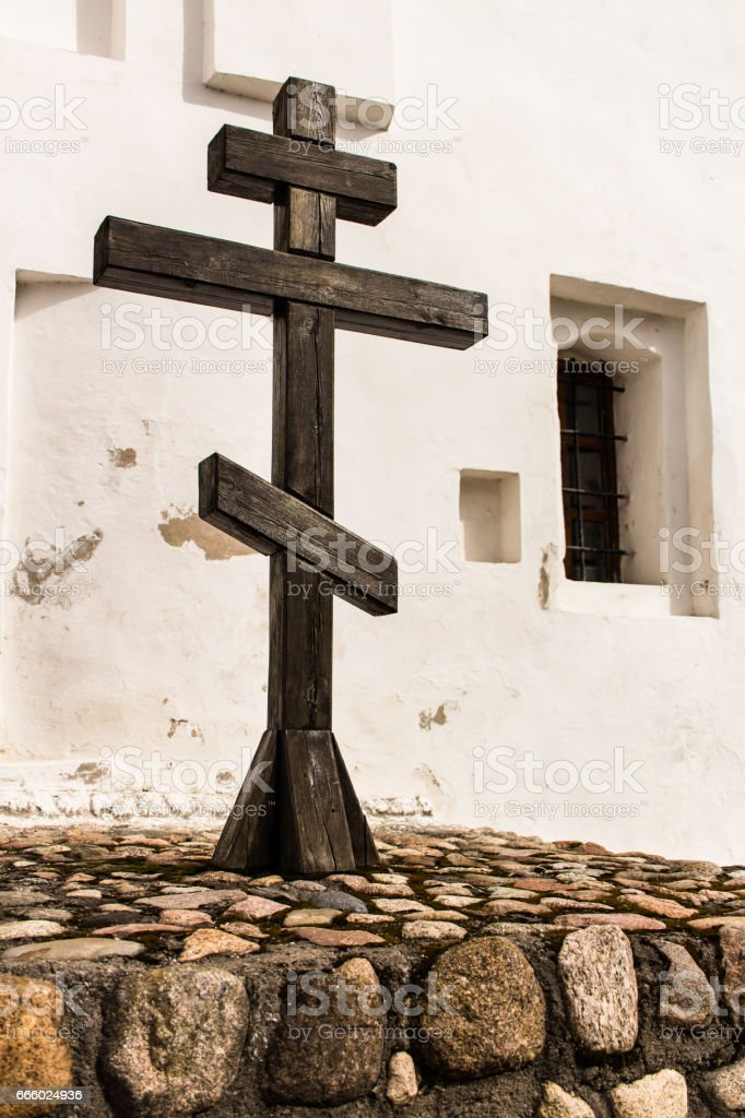 Wooden cross next to the wall of the orthodox church. stock photo