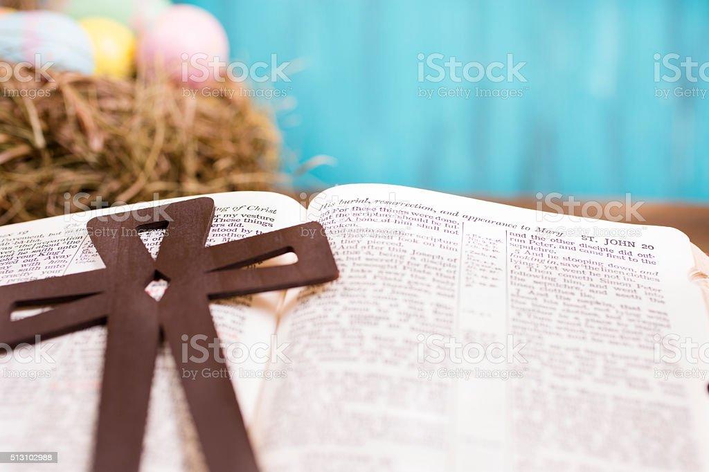 Wooden cross on open Christian Bible. Easter eggs in basket. stock photo