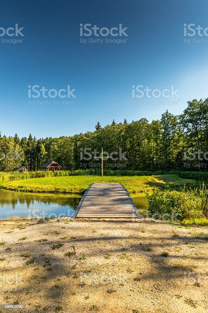 Wooden cross on small island with bridge stock photo