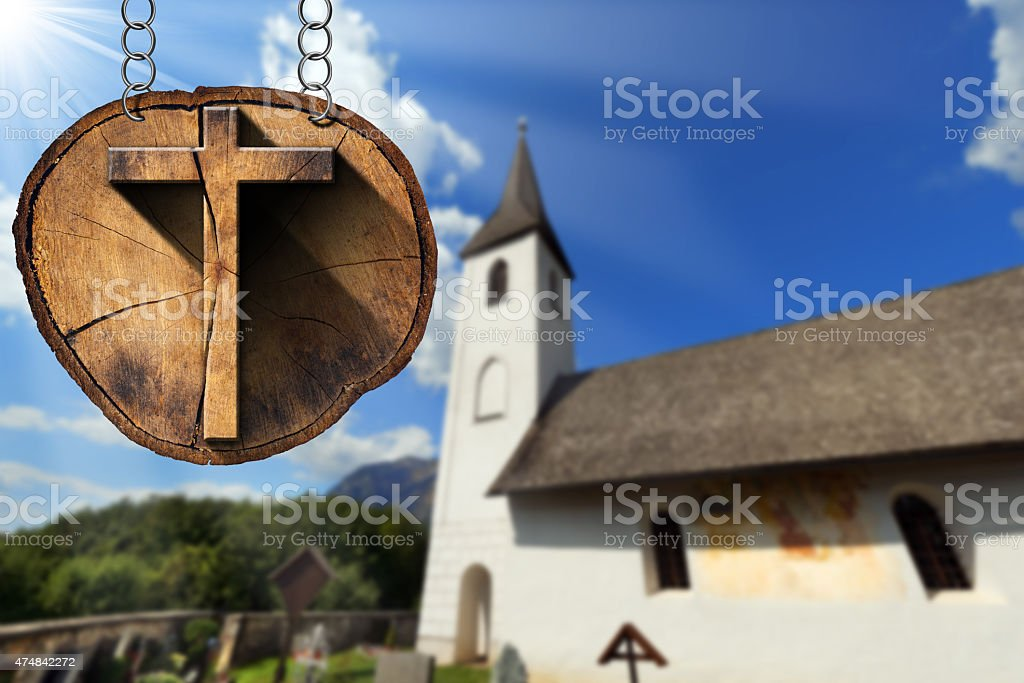 Wooden Cross on Tree Trunk with Small Church stock photo