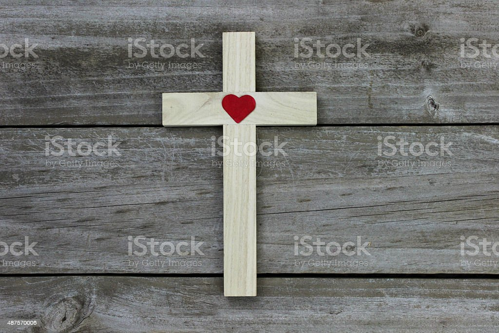 Wooden cross with red heart on rustic background stock photo