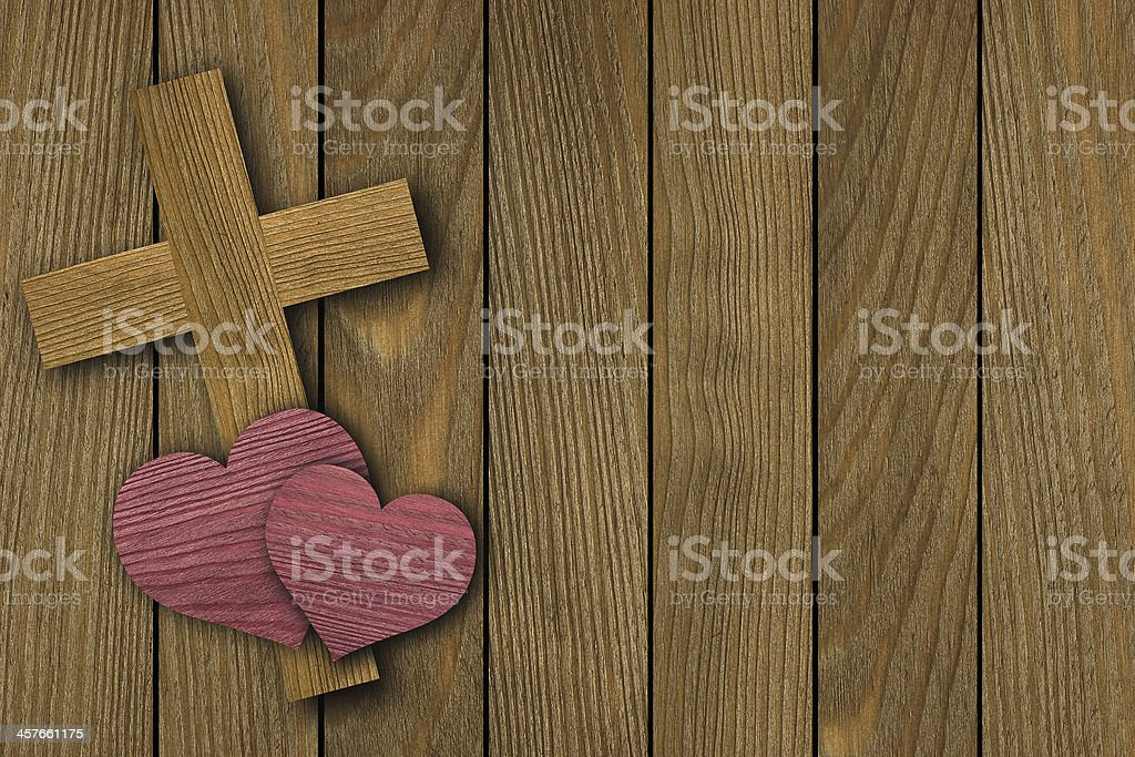 Wooden cross with two hearts on a background of pine planks stock photo