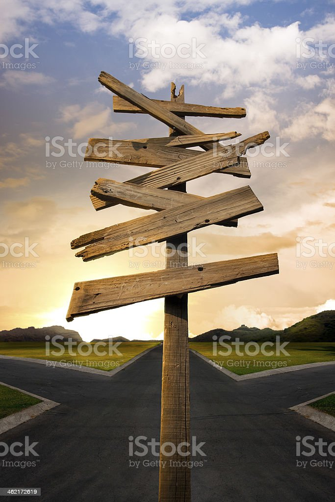 A wooden crossroad signpost with no labels on stock photo
