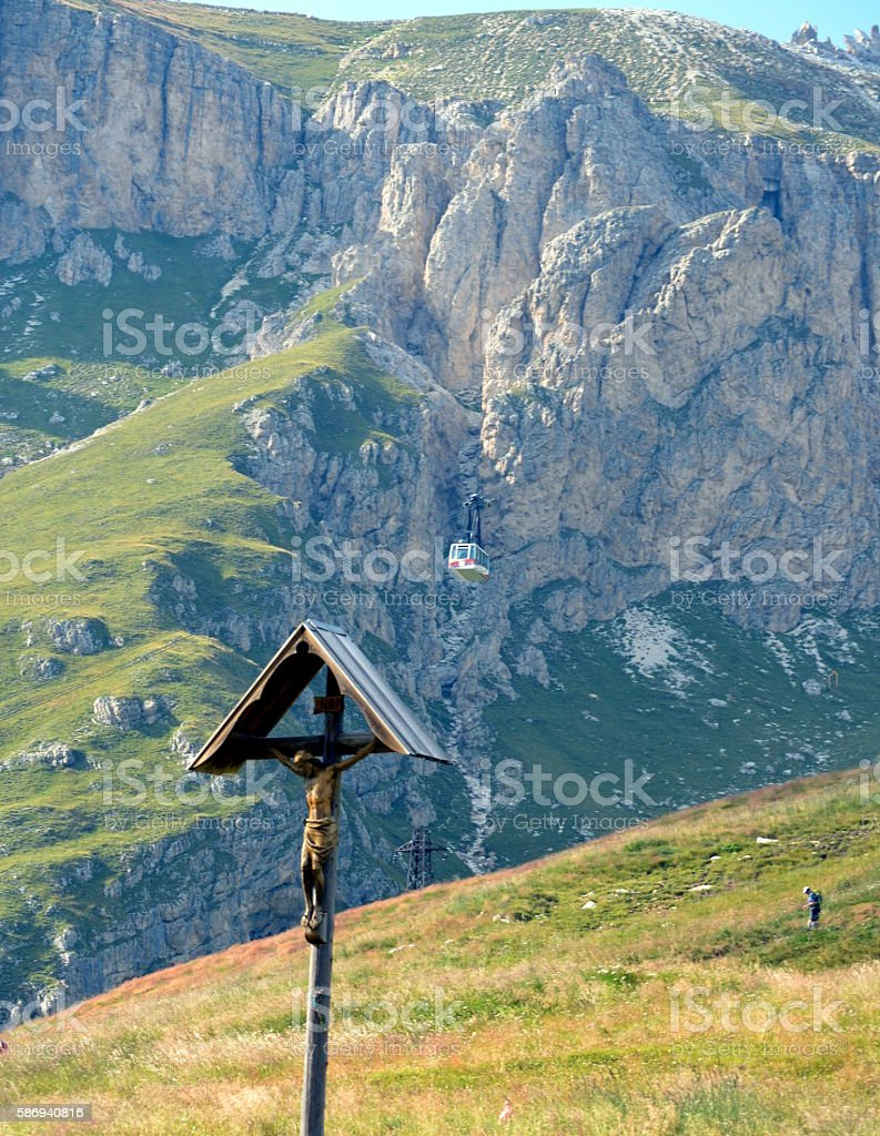 Wooden crucifix in a meadow mountain stock photo