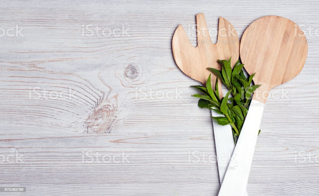 Wooden cutlery with mint leaves on wooden table. Place for your text. Top view stock photo