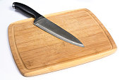 Wooden Cutting Board with Large Knife Laying Isolated on White