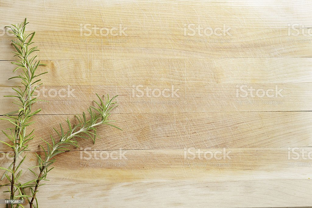 Wooden cutting board with two sprigs of Rosemary on it royalty-free stock photo