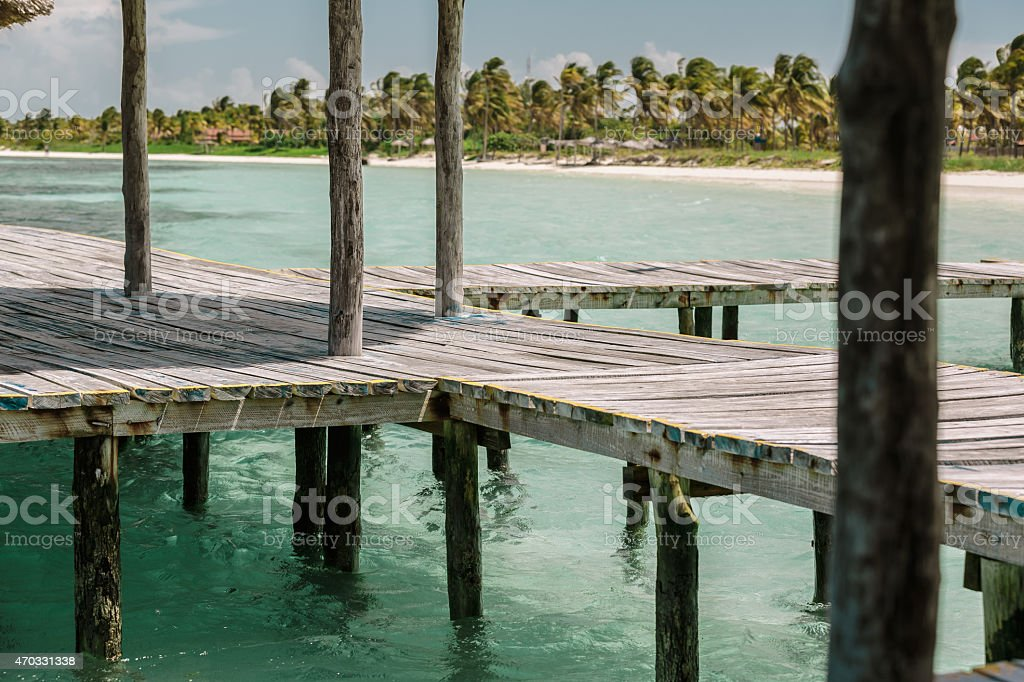 Wooden deck standing in tranquil ocean against beautiful tropical beach stock photo