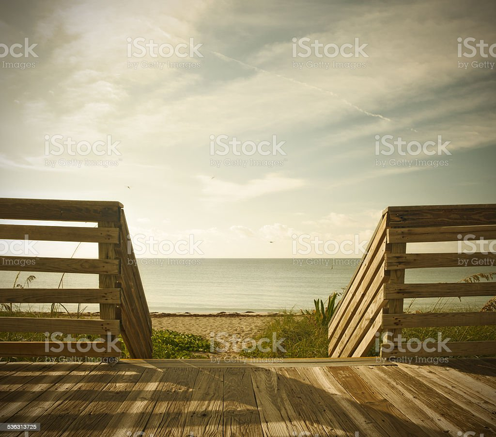 Wooden deck with fence overlooking ocean and the beach stock photo