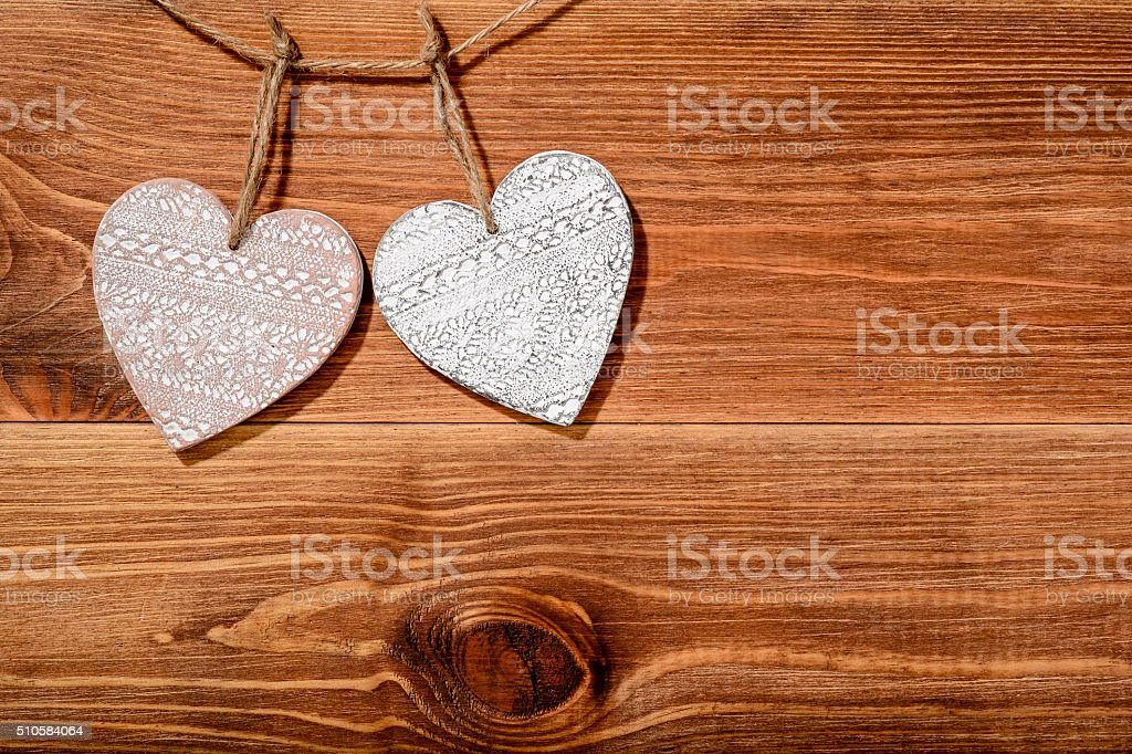 Wooden decorative hearts on brown wooden background. stock photo