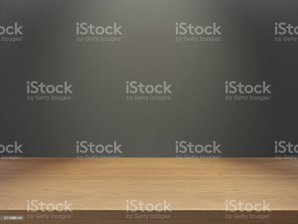 wooden desk with gray wall under light stock photo
