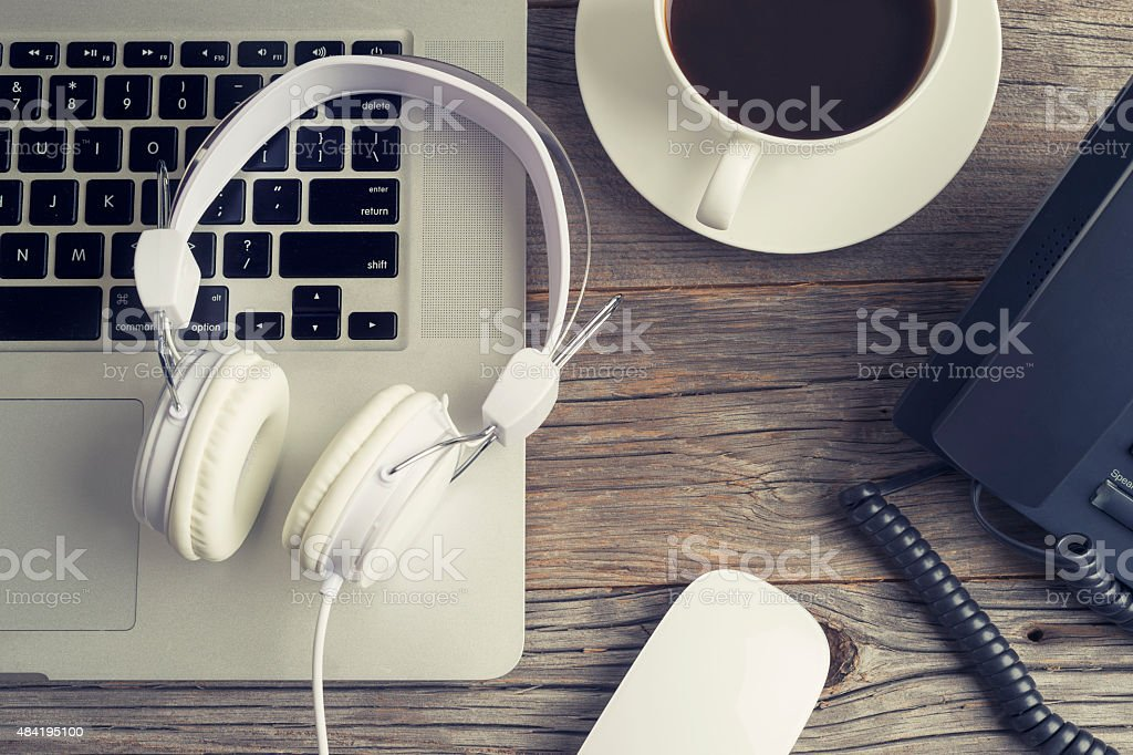 Wooden desk with laptop and headphones. stock photo
