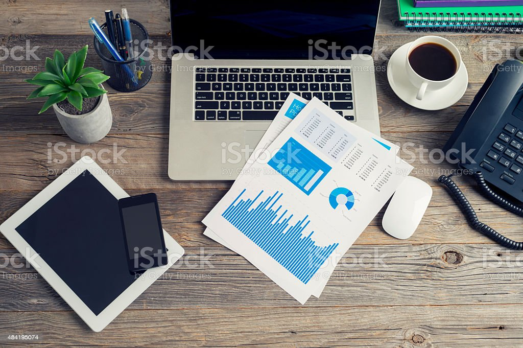 Wooden desk with technology and financial figures. stock photo