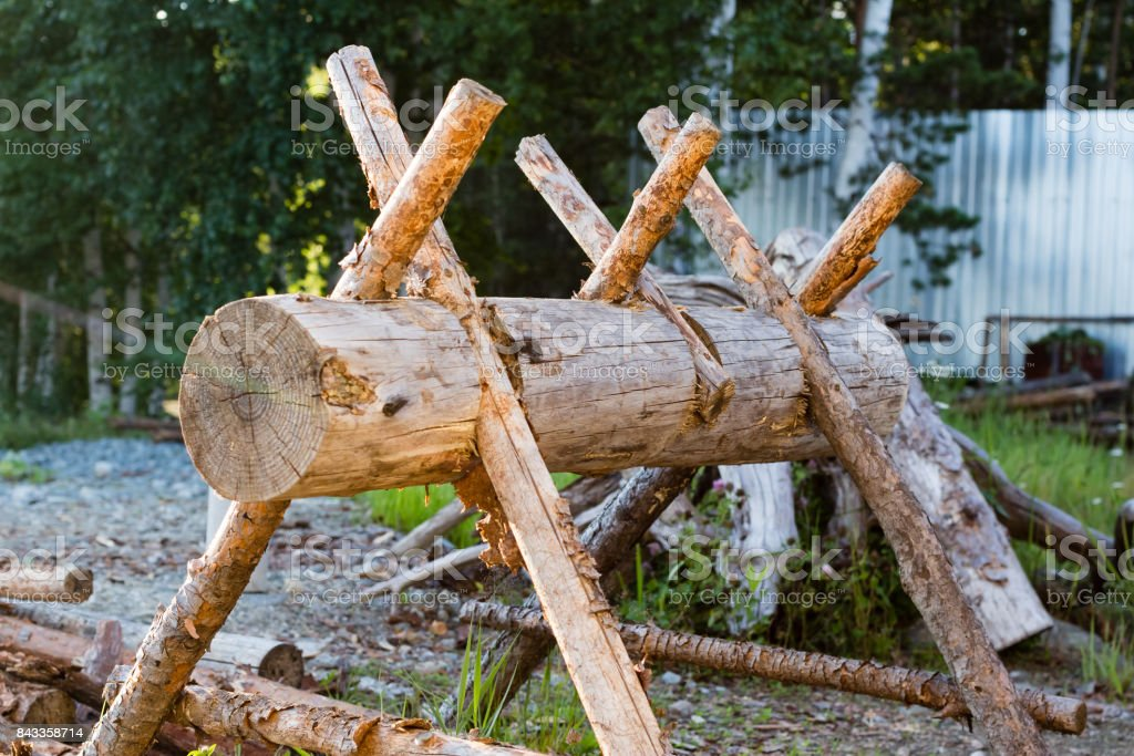 wooden device for cutting firewood and the stack of wooden logs near the wooden fence stock photo