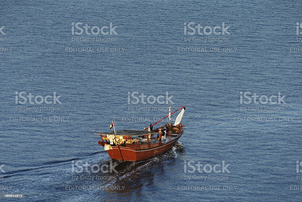 Wooden Dhow Sails into the Dubai Creek at dawn stock photo