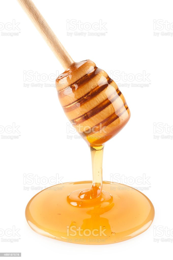 Wooden dipper with honey stock photo