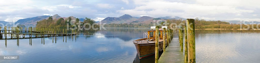 Wooden dock and boat, lake, mountains stock photo