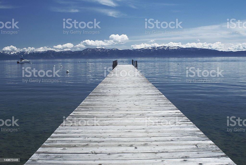 Wooden dock in still lake stock photo