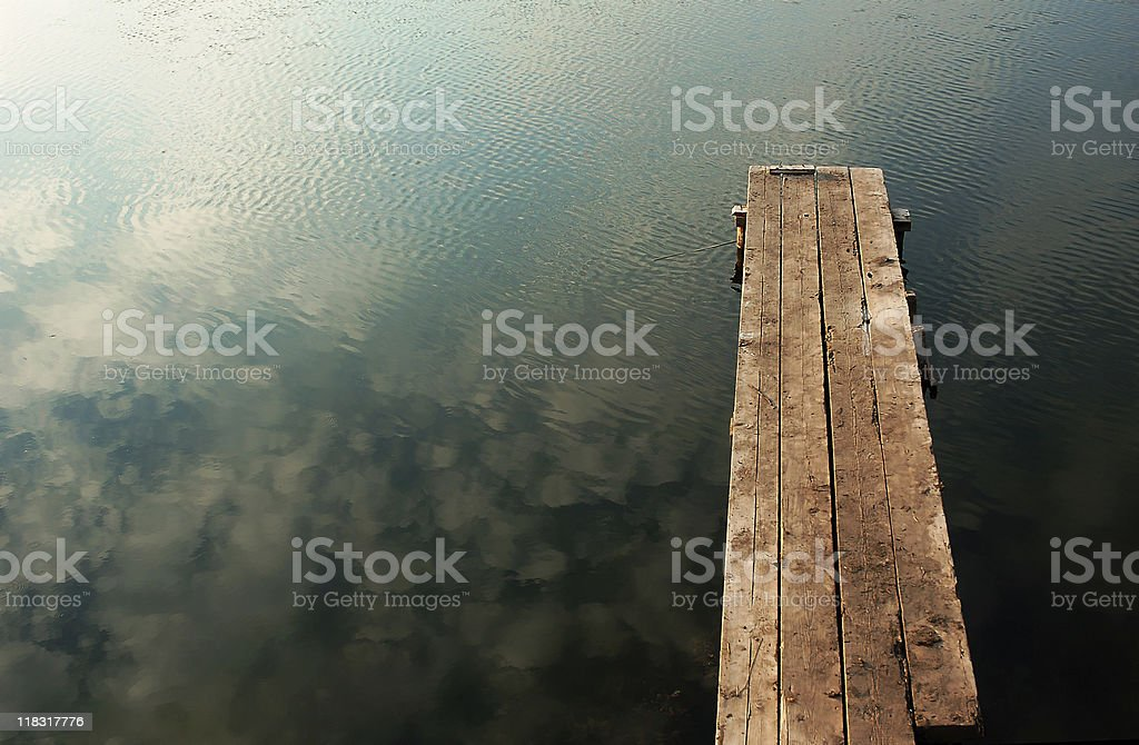Wooden dock next to lake royalty-free stock photo