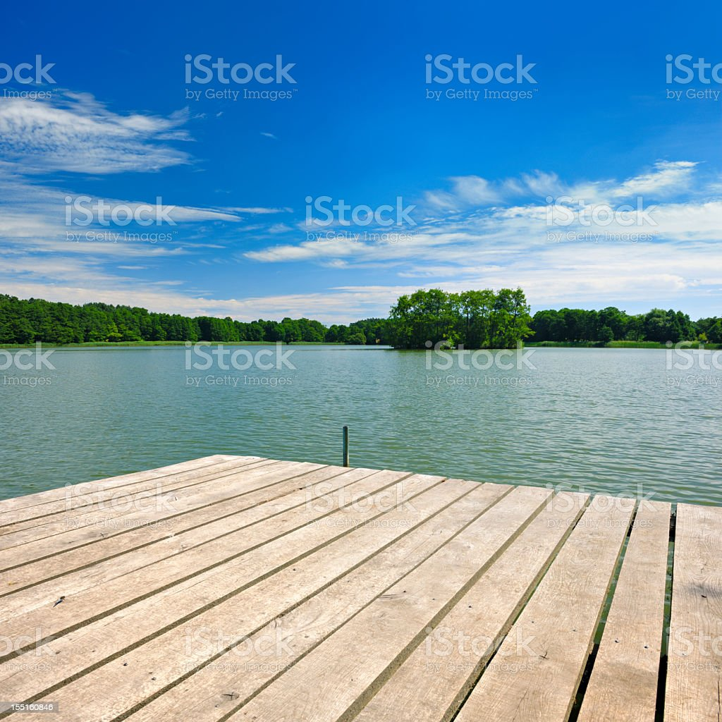 Wooden Dock on Lake amongst the Woods under Cloudy Sky stock photo