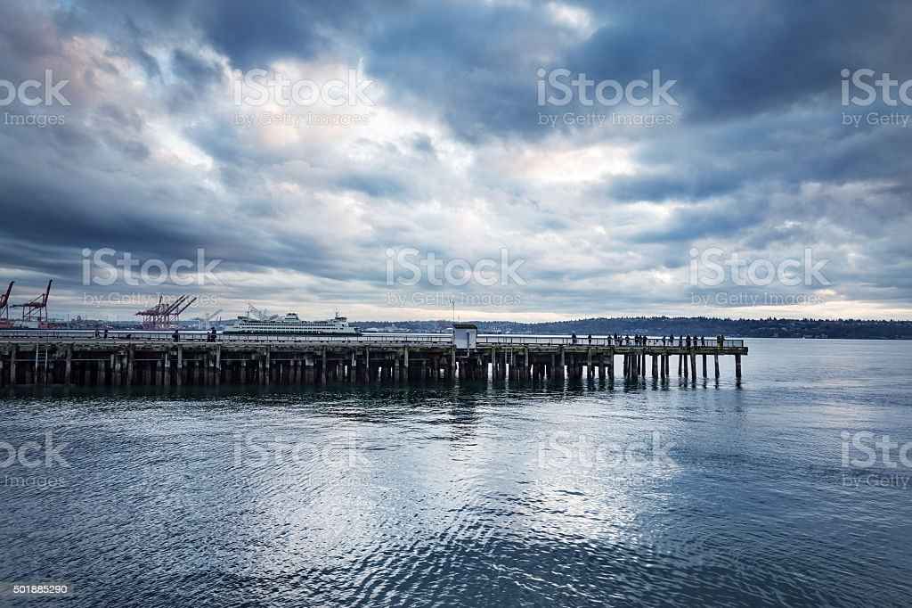 wooden dock on the sea in cloudy sky stock photo