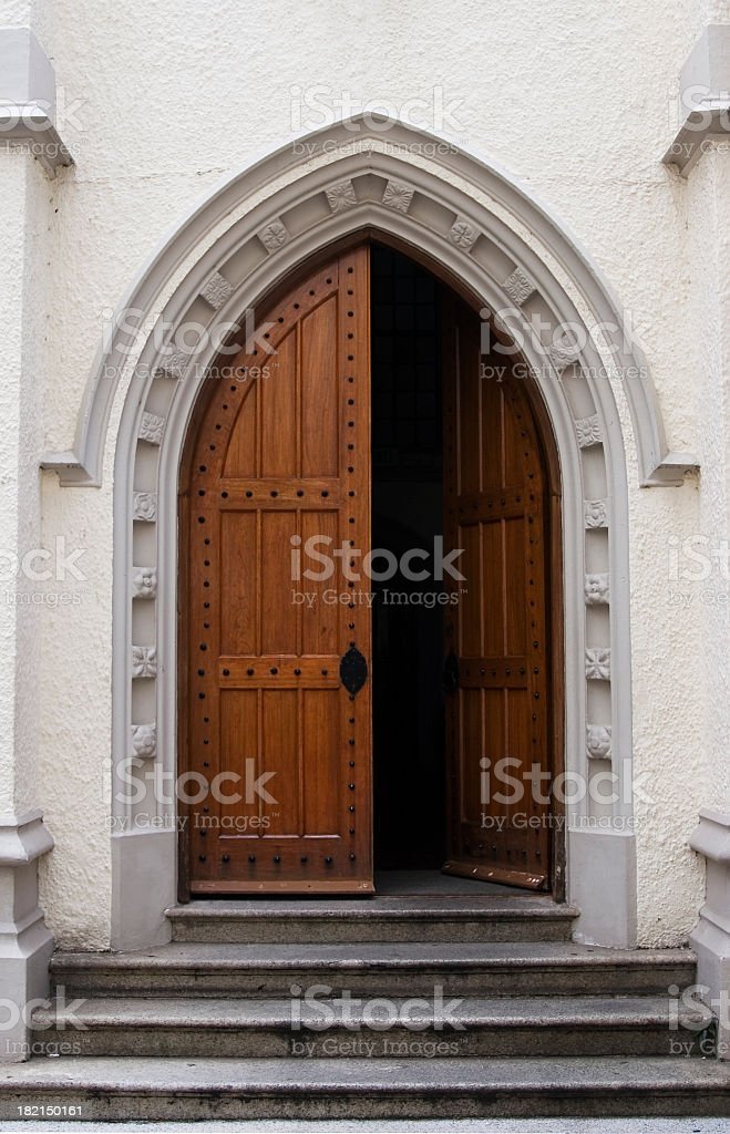 Wooden door half open on a medieval style building entrance stock photo