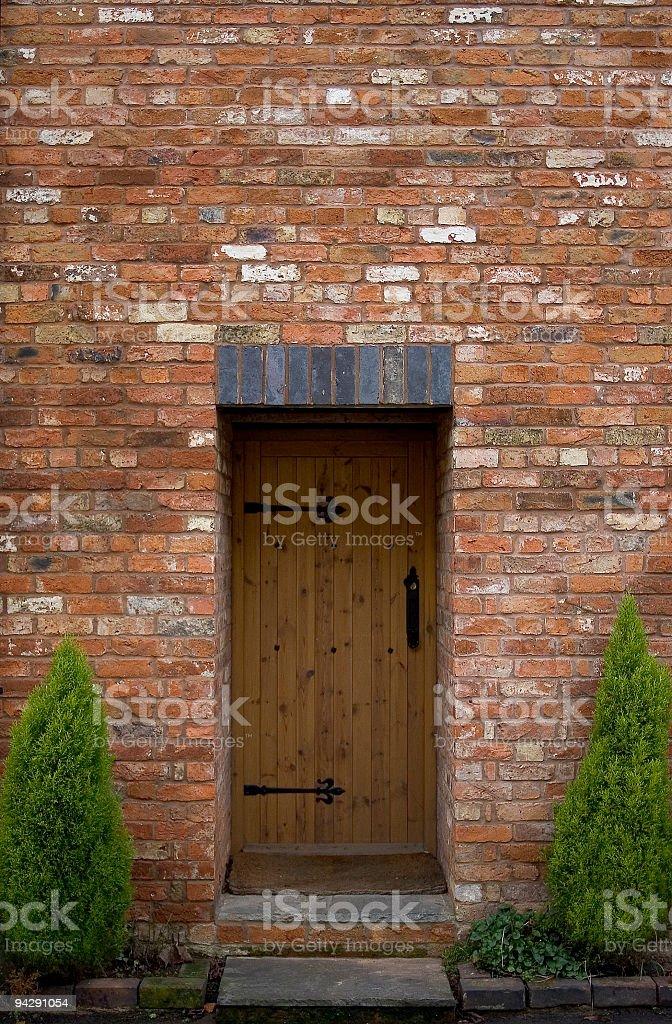 Wooden door in reclaimed brick wall royalty-free stock photo