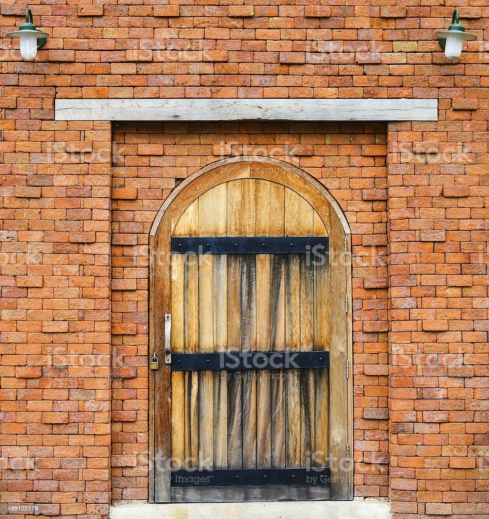 wooden door on red brick wall background stock photo