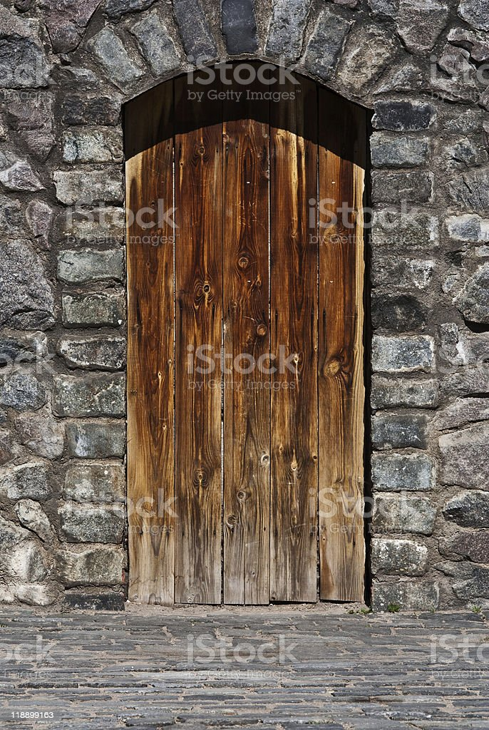 Wooden door on stone wall royalty-free stock photo