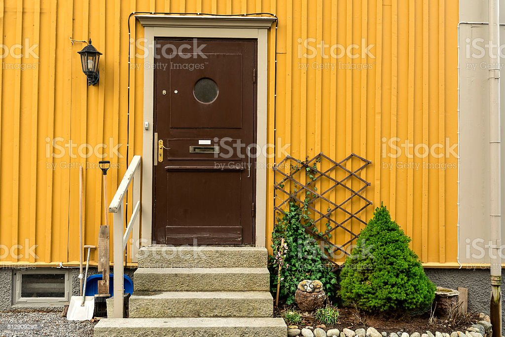 Wooden door with porch and railing, arborvitaes, spruce, garden stock photo