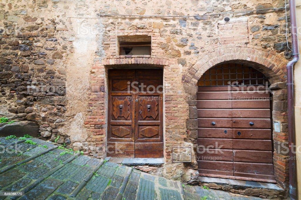 wooden doors in a rustic wall in Montalcino stock photo