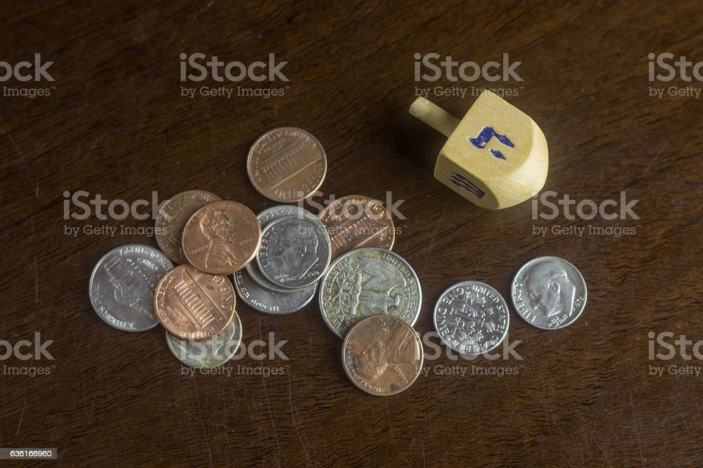 Wooden Dreidel Among Scattered American Coins stock photo