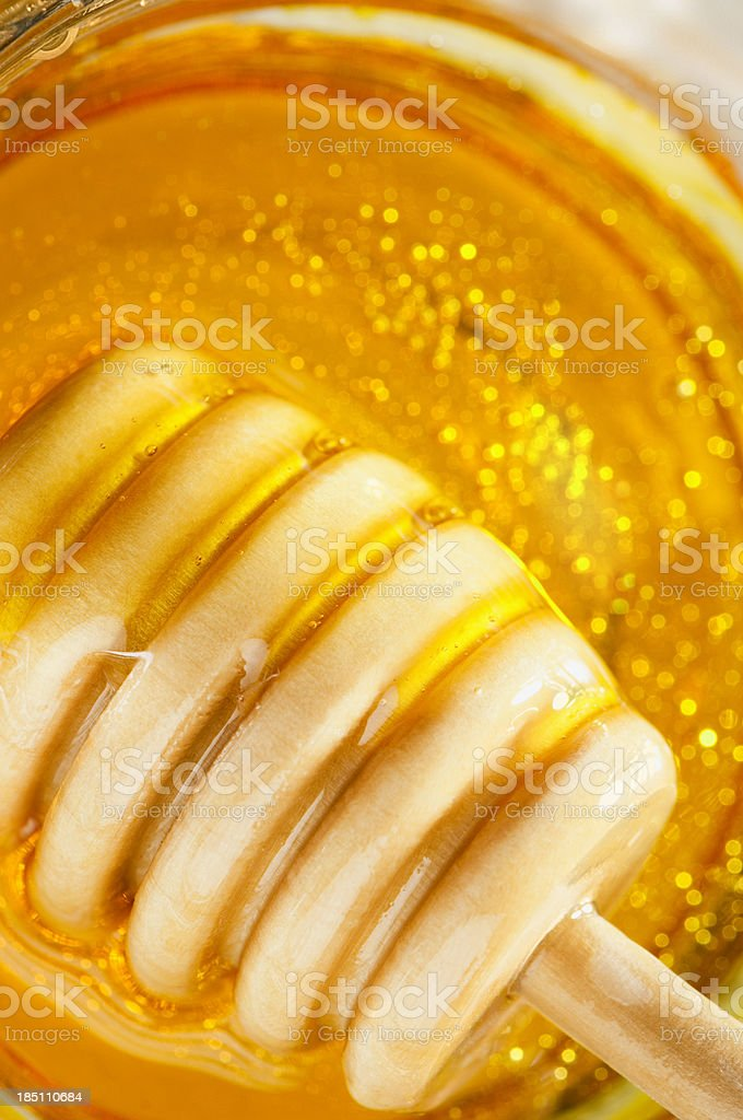 wooden drizzler over pure golden honey with copy space stock photo