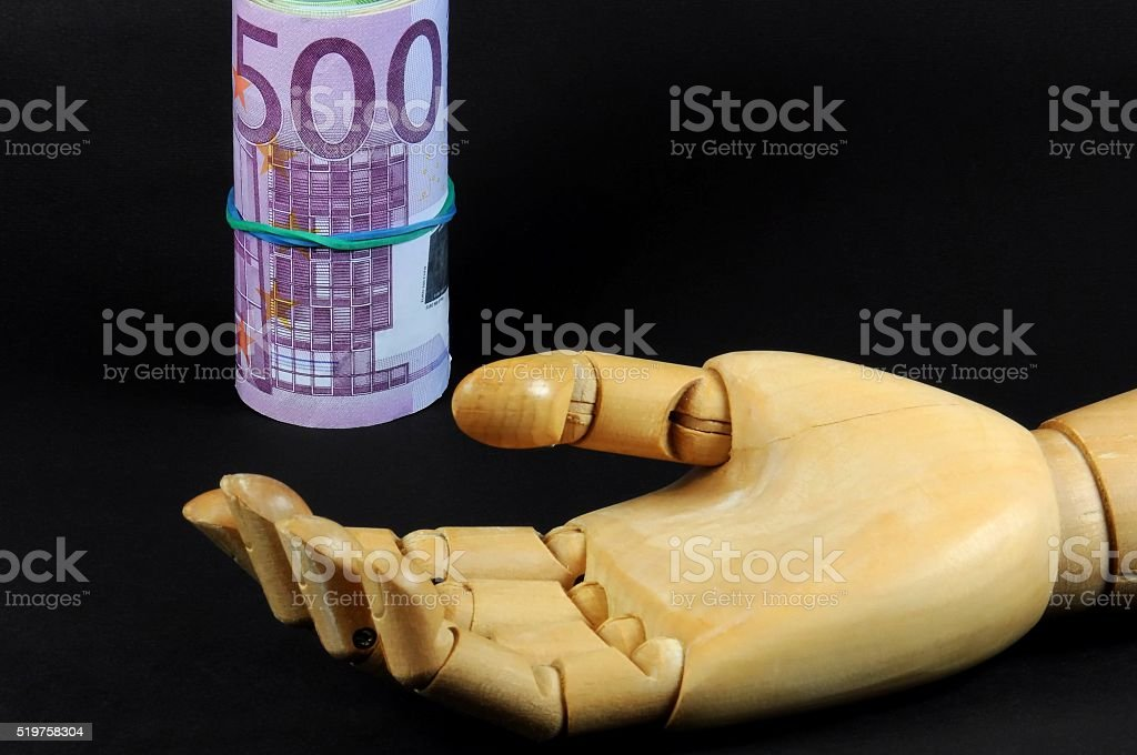 wooden dummy hand painter with euro banknotes roll. stock photo