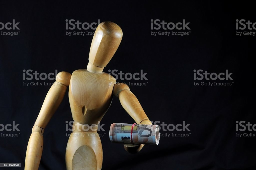Wooden dummy painter with euro banknotes roll. stock photo