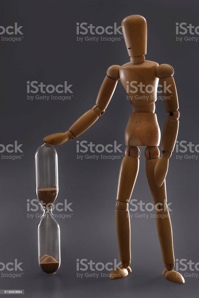Wooden dummy touching houglass stock photo